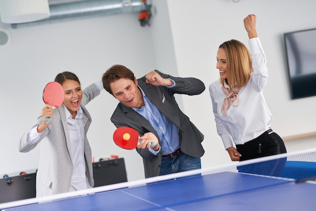 Empresários jogando tênis de mesa em um escritório compartilhado