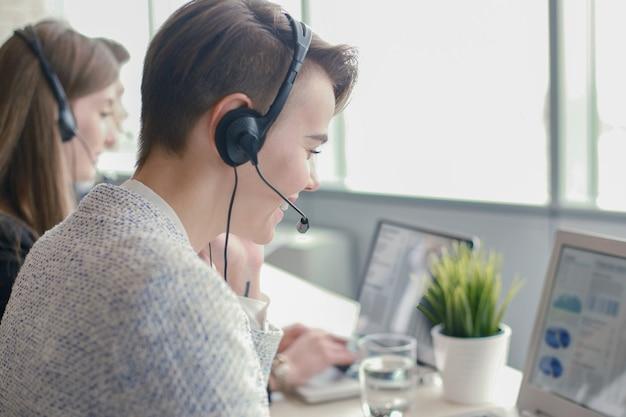 Empresários jovens positivos atraentes e colegas em um escritório de call center.