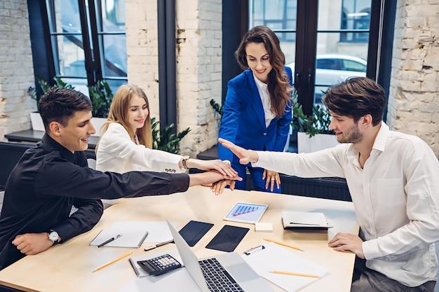 Empresários juntando as mãos no escritório