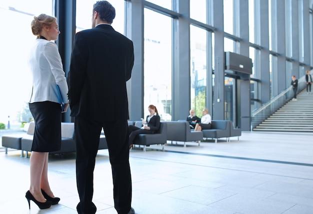Empresários modernos conversando durante o intervalo em pé no corredor de vidro do prédio de escritórios