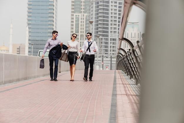 Empresários modernos de terno em dubai marine caminhando para seu escritório