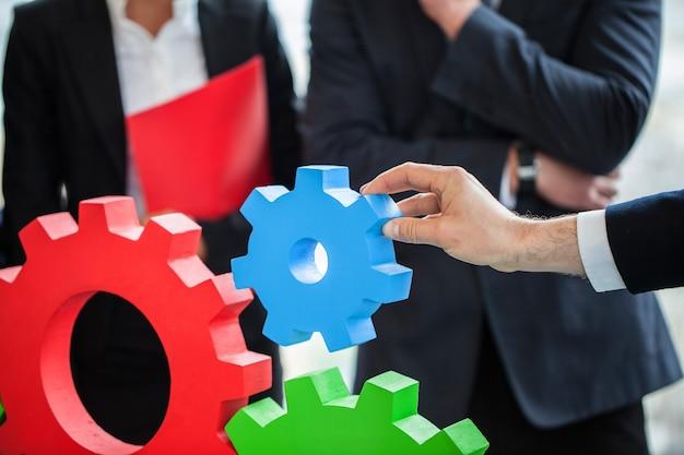 Empresários montando engrenagens, conceito de trabalho em equipe