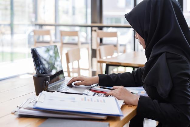 Empresários muçulmanos vestindo hijab preto, trabalhando em uma cafeteria.