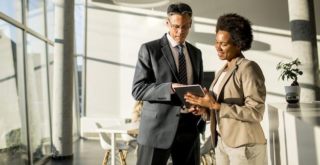 Empresários multiétnicos usando tablet digital enquanto estão no escritório
