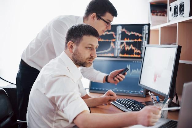 Empresários negociando ações on-line. corretores da bolsa olhando gráficos, índices e números em várias telas de computador. colegas em discussão no escritório de traders. sucesso nos negócios