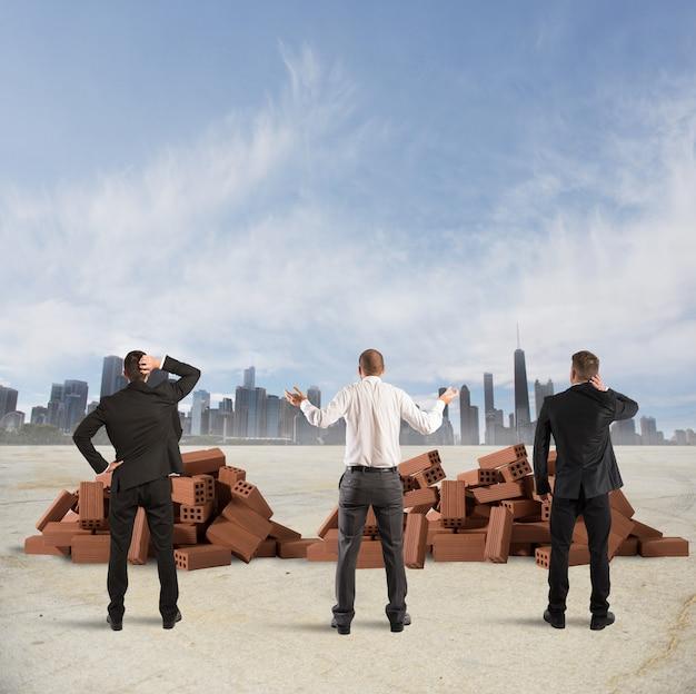 Empresários olham confusos para um tijolo de construção quebrado
