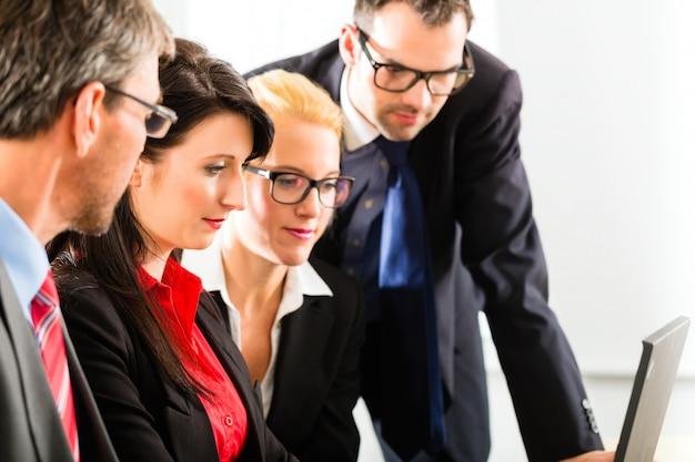 Empresários olhando para a tela do laptop