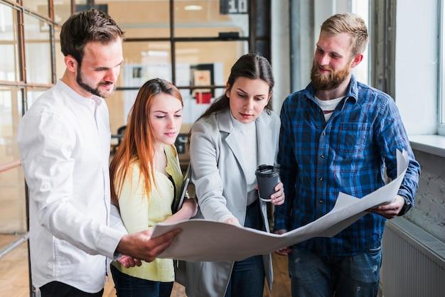 Empresários olhando para impressão azul e discutindo algo