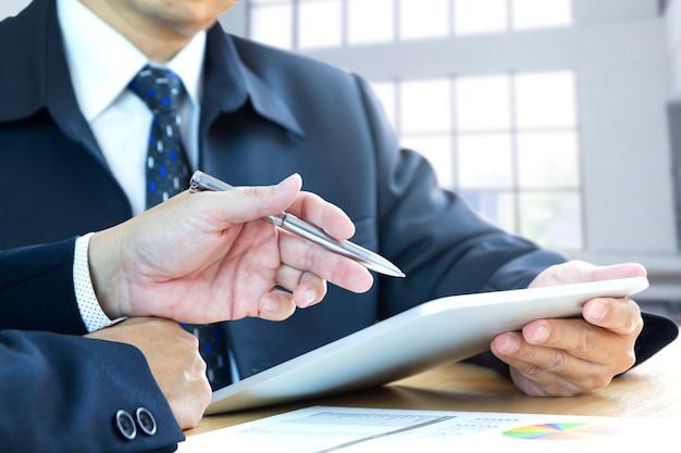 Empresários ou investidores que revisam o retorno do investimento em um dispositivo móvel tablet. espaço de cópia lateral incluído.