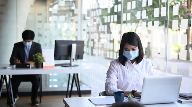 Empresários ou trabalhador de escritório usando máscara protetora e trabalhando juntos no escritório.