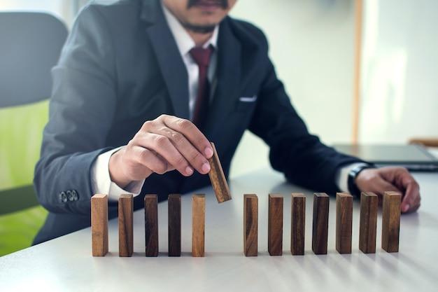 Empresários pegar peças de dominó de uma linha.