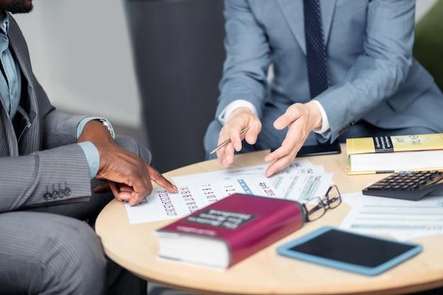Empresários perto de calendário. dois empresários sentados à mesa e discutindo a próxima negociação perto do calendário