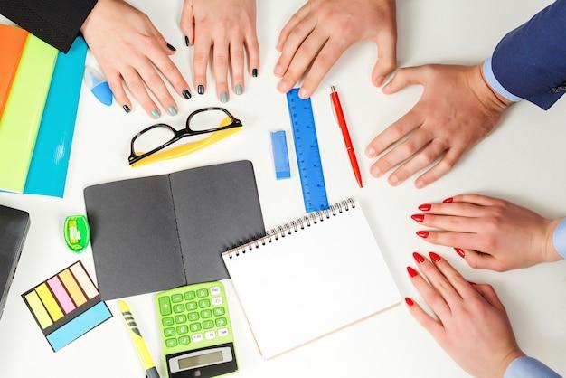 Empresários planejando um novo projeto. mulher de negócios e reunião de escritório do empresário. conceito de trabalho em equipe. tripulação de jovens colegas de trabalho closeup trabalhando com nova inicialização durante a reunião.