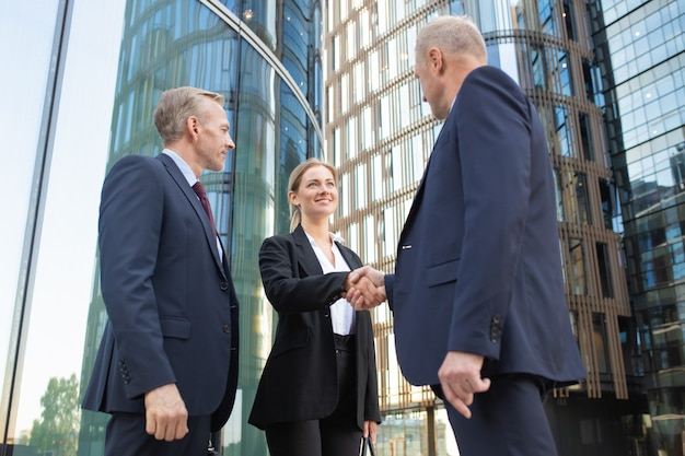Empresários positivos e seguros reunidos na cidade, apertando as mãos perto de prédio de escritórios. tiro de ângulo baixo. conceito de comunicação e parceria