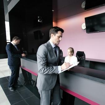 Empresários preenchendo formulários na recepção