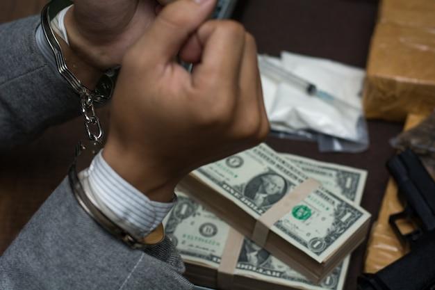 Empresários presos, homem com algemas com dinheiro e drogas.