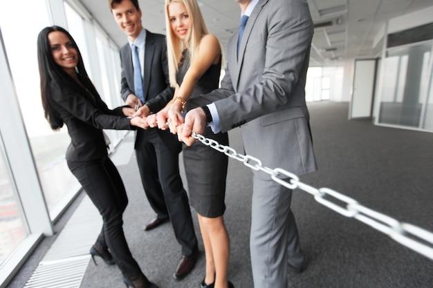 Empresários puxando a corrente, conceito de união do trabalho em equipe