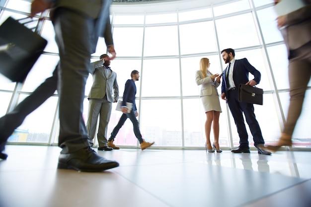 Empresários que andam através do escritório
