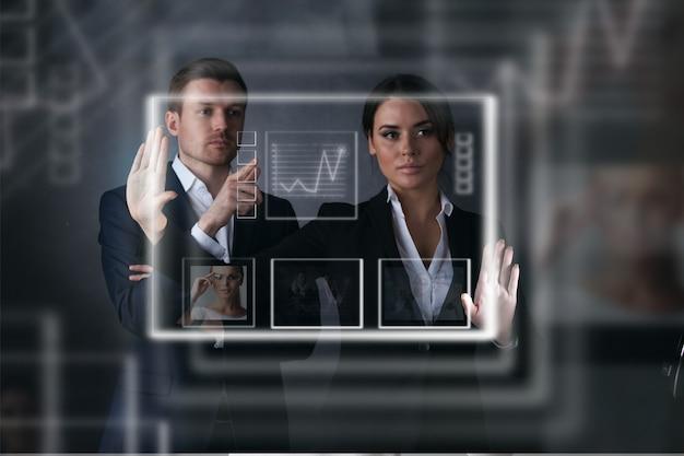 Empresários que trabalham com display virtual com gráficos e dados