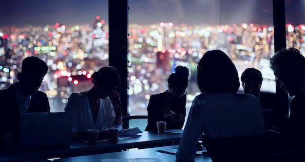 Empresários que trabalham juntos no escritório à noite. conceito de trabalho em equipe e parceria.