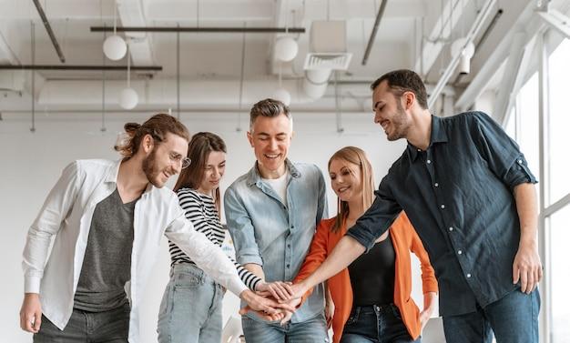 Empresários reunidos no escritório apertam a mão