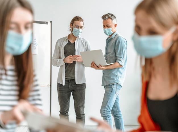 Empresários reunidos no escritório usando máscaras