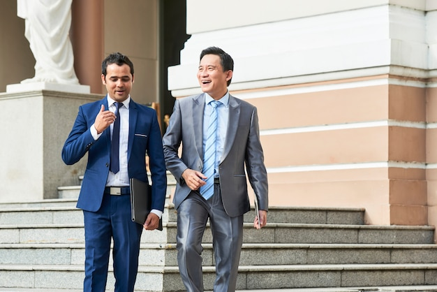 Empresários saindo do prédio de escritórios