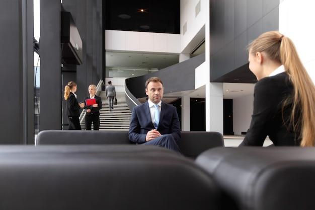 Empresários se encontrando no saguão de um edifício moderno