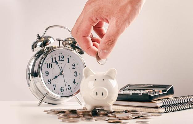 Empresários seguram moedas no cofrinho é uma ideia de economia de dinheiro para contabilidade financeira.