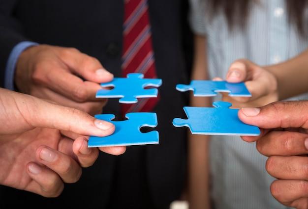 Empresários segurando peças do quebra-cabeça. conceito de solução de problema