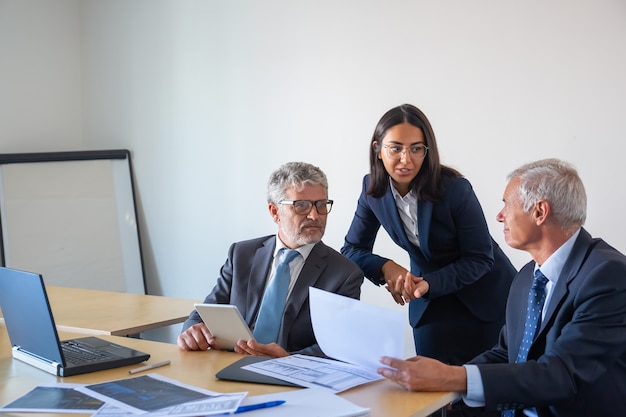 Empresários seniores e jovem assistente trabalhando com estatísticas. colegas de conteúdo sério em trajes de escritório sentados à mesa com laptop, documentos e tablet. conceito de gestão e parceria