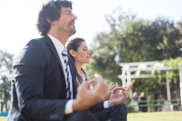 Empresários sentado com as pernas cruzadas ao ar livre