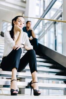 Empresários sentados na escada e pensando. enterior moderno