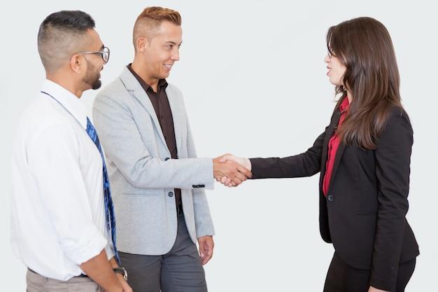 Empresários sorridentes apertando as mãos na reunião