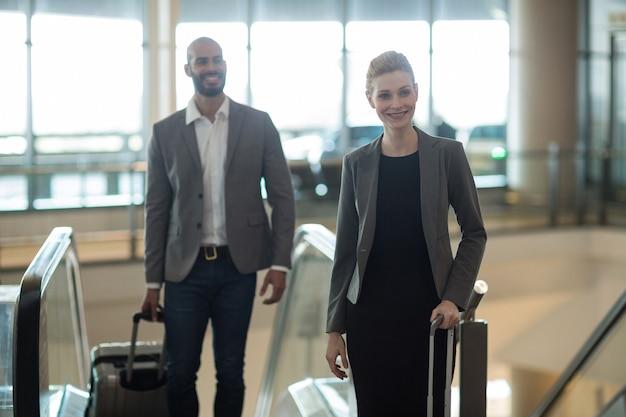 Empresários sorridentes com bagagem em frente a uma escada rolante