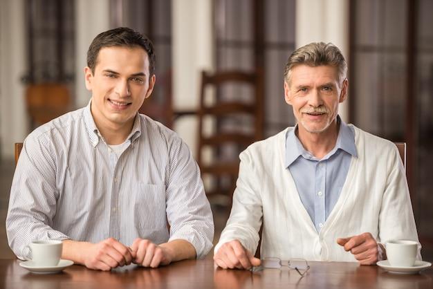 Empresários sorridentes em camisas, sentado à mesa de madeira.