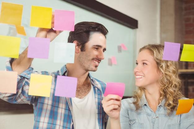 Empresários sorridentes tocando notas pegajosas no vidro no escritório