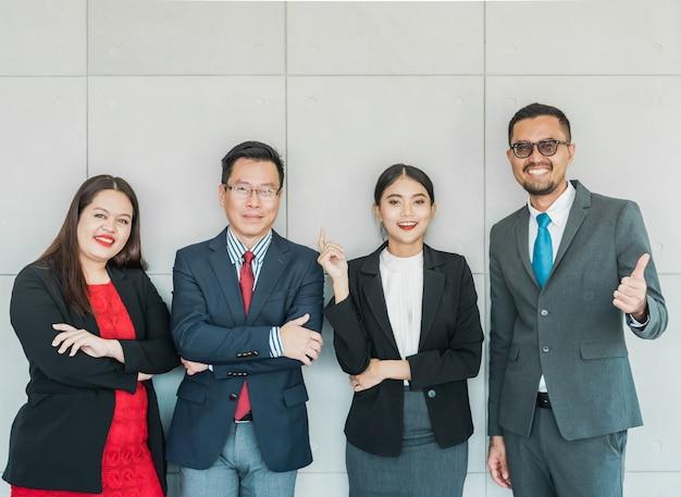 Empresários, sorrindo e de pé em seu escritório