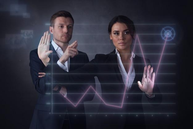 Empresários tocando em um gráfico que indica o crescimento no display virtual