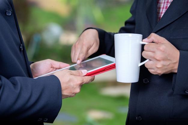 Empresários tomando café e descrevendo o trabalho no laptop