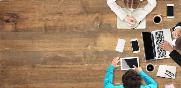 Empresários trabalhando com laptop e gadgets, vista superior em fundo de madeira