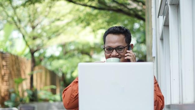 Empresários trabalhando em computadores tomando café com telefone