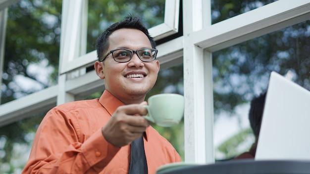 Empresários trabalhando em computadores tomando café e sorrindo
