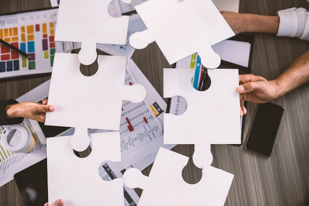 Empresários trabalhando juntos para construir um quebra-cabeça. conceito de trabalho em equipe, parceria, integração e startup.