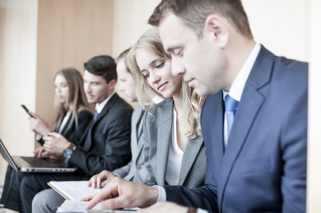 Empresários trabalhando juntos, sentados em uma fileira no saguão e segurando um laptop e documentos sobre os joelhos