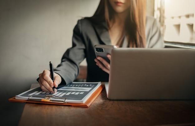 Empresários trabalhando na área de trabalho com smartphones e planilhas de dados na mesa.