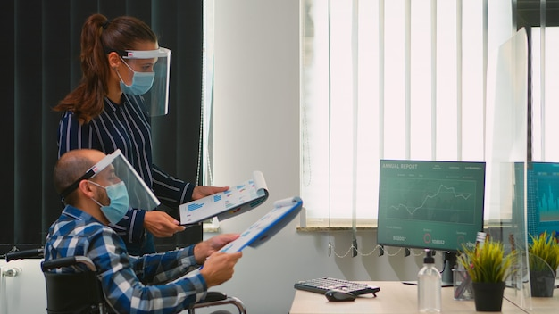 Empresários usando máscara protetora na nova estratégia de tomada de escritório normal, empresário sentado em cadeira de rodas equipe trabalhando no espaço de trabalho profissional em empresa corporativa durante a pandemia covid-19.