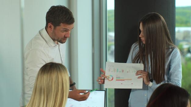 Empresários vestidos casualmente discutindo ideias no escritório. gerente feminina conduz reunião de brainstorming no escritório de design