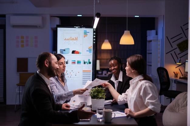 Empresários workaholics debatendo ideias para empresas financeiras, analisando papelada de estratégia tarde da noite na sala de reuniões do escritório de negócios