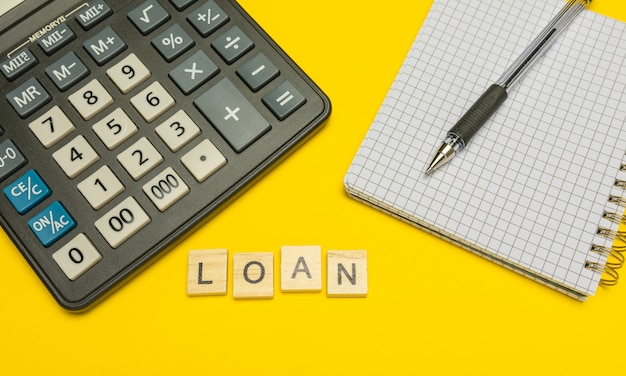 Empréstimo de palavra feito com letras de madeira na calculadora amarela e moderna com caneta e caderno.